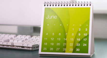 Image of a green monthly calendar next to a desktop computer.