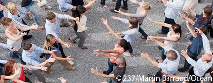 Two large groups of people walking towards eachother with their arms outstretched.