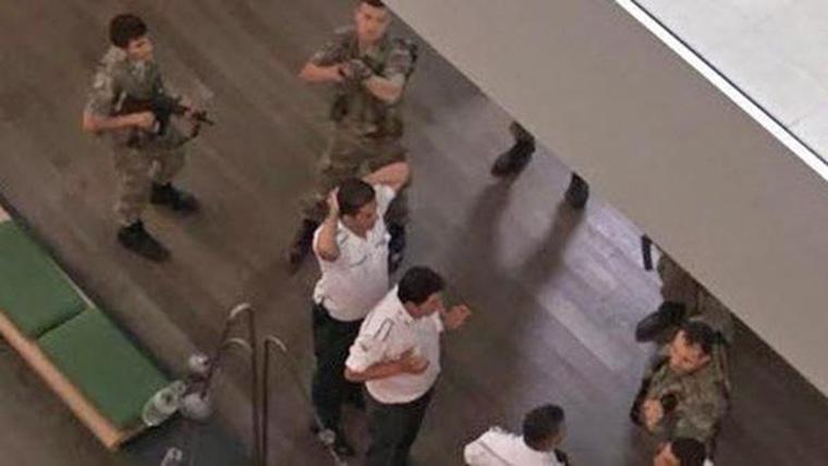 Coup members wielding machine guns take Hürriyet staff hostage and raid the newsroom.