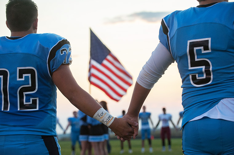Freeman's Dakota Steiger (72) wore an armband memorialising fellow student Sam Strahan as he joined hands with teammate Jace Phelan (5) in remembrance before the start of a football game against Medical Lake on Friday, September 18, 2017, at Freeman High School in Rockford, Washington (Photo by Tyler Tjomsland/The Spokesman-Review)