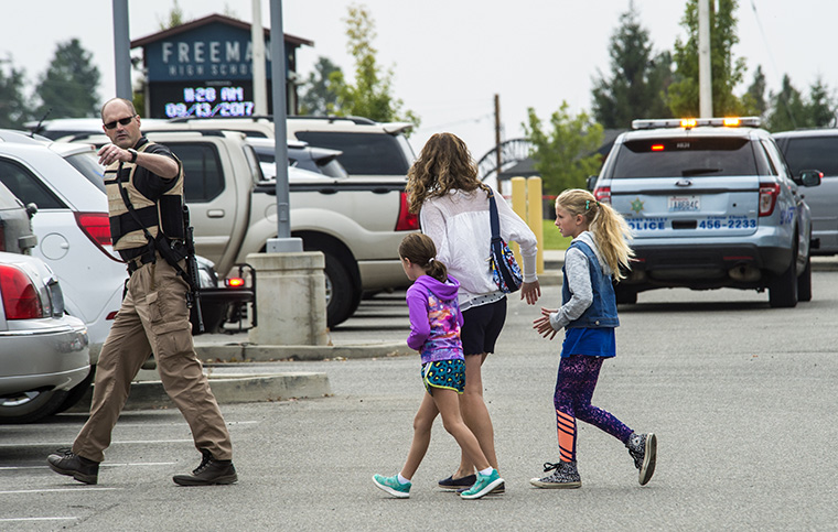 A law enforcement officer leads a family away from Freeman High School after a shooting, September 13, 2017. (Photo by Dan Pelle/The Spokesman-Review)