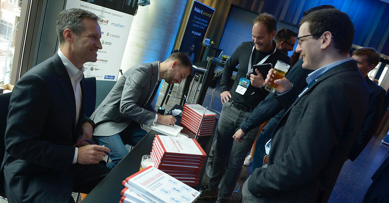 "Matt Lindsay and Matthijs van de Peppel sign copies of their book, ""How to Succeed in the Relationship Economy,"" at the INMA symposium."