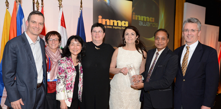 The New York Times team receives the INMA Awards competition's top prize from INMA President Ravi Dhariwal of the Times of India.