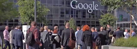 A group of people standing outside a Google office building.